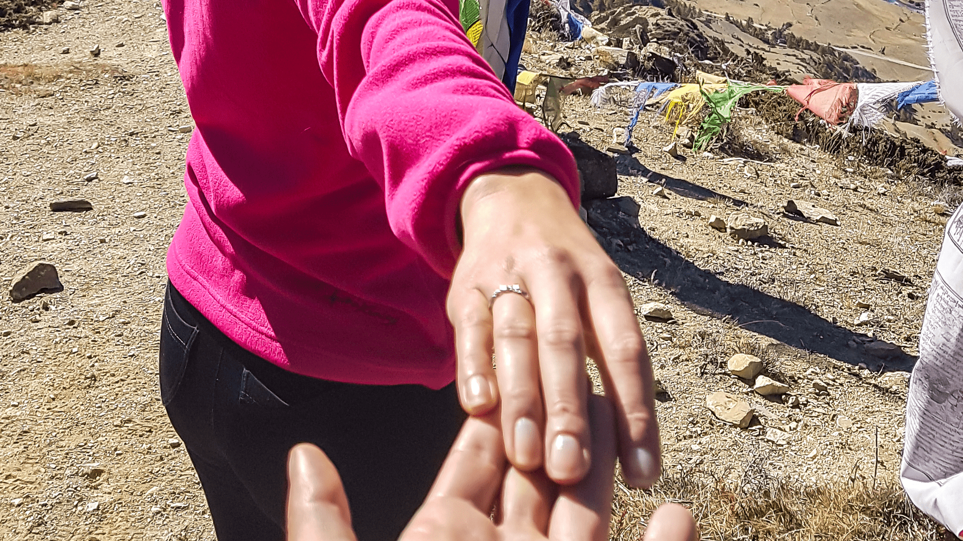 a married couple holds hands while hiking and show off wedding band