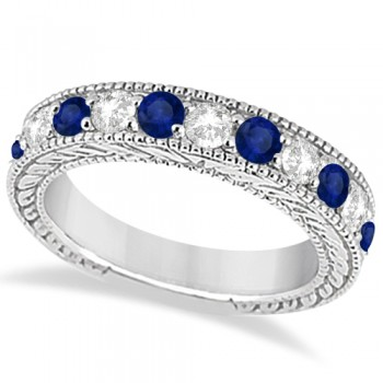 Antique Diamond & Sapphire Wedding Ring Band 18k White Gold (1.46ct) This heirloom diamond wedding ring is expertly crafted in 18kt white gold, showcasing hand-set diamonds and blue sapphires, milgrain edges, and scroll work (filigree).The antique-style ring features 11 brilliant-cut round stones: six bold sapphires alternate with five diamonds of clear G-H color and VS2-SI1 clarity for stunning effect.The stones are mounted in a bead setting and total 1.46ct.This designer bridal wedding band is also available in other metals.