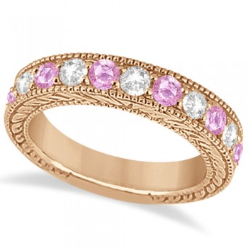 Antique Diamond & Pink Sapphire Wedding Ring in 14k Rose Gold (1.46ct) Hand crafted in 14kt rose gold (pink gold), this vintage style diamond wedding ring showcases 11 round cut stones for a total  of 1.46 carats.The 5 diamonds are of clear G-H color and VS2-SI1 Clarity, alternating with six beautiful pink sapphires, all mounted in a bead setting.The art deco wedding band features filigree (scroll work) and milgrained edge engravings for a classic look that never goes out of style.This one-of-a-kind bridal wedding ring is available in alternate metals as well.