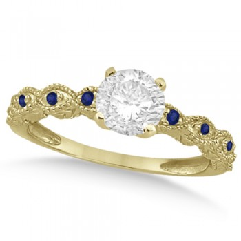 Vintage Diamond & Blue Sapphire Engagement Ring 18k Yellow Gold 1.50ct Dazzle her with this vintage style diamond and blue sapphire engagement ring, preset with approximately 1.50 total carats of expertly chosen gems.This ring, proudly made in the USA, features a prong set conflict free round diamond of approximately 1.30 carats with eight pave set blue sapphire side stone accents. These side stone feature an approximate total weight of 0.18 additional carats.This stunning antique setting of 18k yellow gold makes this diamond and blue sapphire twisted shank engagement ring the perfect choice for those brides looking for an alternative to the ordinary diamond ring.