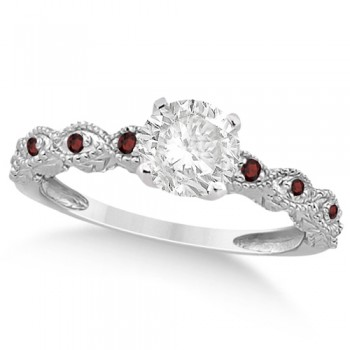 Vintage Diamond & Garnet Engagement Ring 18k White Gold 1.50ct Dazzle her with this vintage style diamond and garnet engagement ring, preset with approximately 1.50 total carats of expertly chosen gems.This ring, proudly made in the USA, features a prong set conflict free round diamond of approximately 1.30 carats with eight pave set garnet side stone accents. These side stone feature an approximate total weight of 0.18 additional carats.This stunning antique setting of 18k white gold makes this diamond and garnet twisted shank engagement ring the perfect choice for those brides looking for an alternative to the ordinary diamond ring.